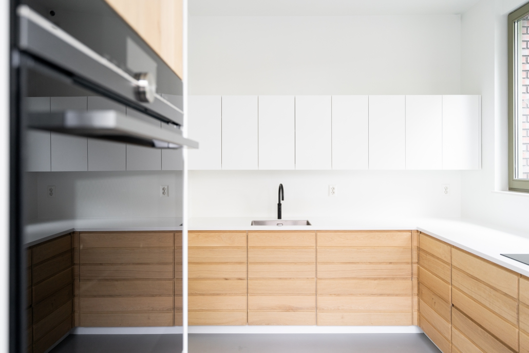 Een keuken met eikenhouten fronten, wit mat spuitwerk en Hi Macs blad